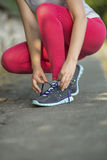 Young  girl tying shoelaces on sneakers cross-country. Royalty Free Stock Images