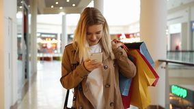 Young girl types something in her phone walking around the mall with shopping bags