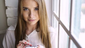 Young girl typing message on smartphone. Adult woman with smile and white shirt typing message on digital gadget and looking at camera indoors near window at new stock video