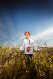 Young girl in ukrainian clothes walking at wheat field Royalty Free Stock Photography