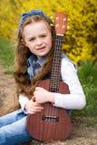 Young girl  with ukulele. Young kid with ukulele, outdoor portrait of pretty girl playing the ukulele sitting on the grass Stock Photo