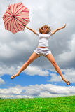 Young girl with an umbrella. Young girl jumping with an umbrella Royalty Free Stock Photography