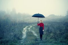 Young girl with umbrella in autumn field. Blond young girl with umbrella in autumn field stock photography