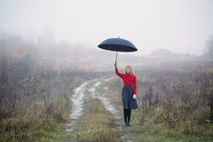 Girl with umbrella in autumn field. Young girl with umbrella in autumn field royalty free stock photography