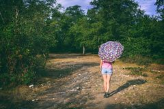 Young girl with an umbrella on a country road Stock Photography