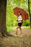 Young girl with an umbrella in park royalty free stock images