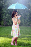 Young girl with umbrella in the rain Stock Image