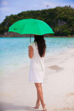 Young girl with umbrella on white beach Royalty Free Stock Photos