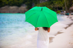 Young girl with umbrella on white beach Royalty Free Stock Photography