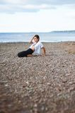 A young girl in the unbuttoned white blouse and black trousers p. Hysical exercises on the beach of pebbles Stock Image