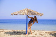 Young girl under umbrela in the shade. Young girl on the beach under umbrella Royalty Free Stock Images