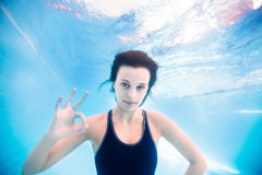 Young girl underwater showing ok sign stock photo