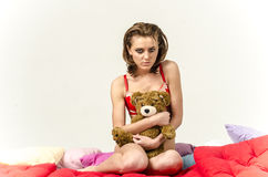 Young girl in underwear in bed crying and wiping tears smearing her hands Royalty Free Stock Images