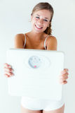 Young girl in underwear holding scales. Royalty Free Stock Image