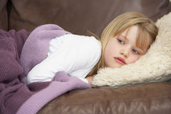 Young Girl Unwell Lying On Sofa Royalty Free Stock Photography