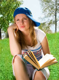 Young girl unwilling to read. Pretty young girl reading a book outdoor Stock Image
