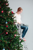 Young girl unwrapping Christmas decoration. Sitting on a ladder Royalty Free Stock Photo