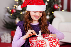 Young girl unwrapping her Christmas present Royalty Free Stock Image