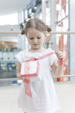 Young girl unwrapping ribbon on present Stock Photo