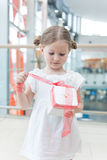 Young girl unwrapping ribbon on present Royalty Free Stock Photo