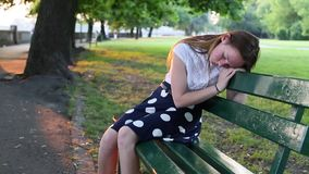 Young girl upset sitting on a Park bench. Problems of teenagers. stock video