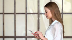 Young girl use cellphone for browsing social networks or messaging online. Young girl in white clothing use portable gadget for browsing social networks or stock video