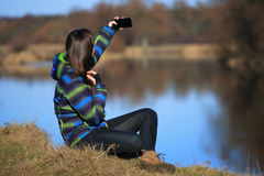 Young girl use her mobile for making photo Royalty Free Stock Photo