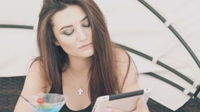 Young girl uses digital tablet and resting on beach lounge. Slowly stock video