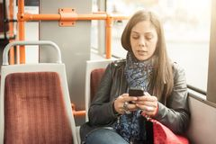 Young girl uses a mobile phone in the city bus stock image