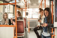 Young girl uses a mobile phone in the city bus. Technology cell phone isolation. Internet and social media Royalty Free Stock Photos