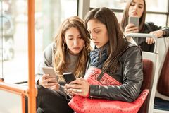 Young girl uses a mobile phone in the city bus Stock Photos