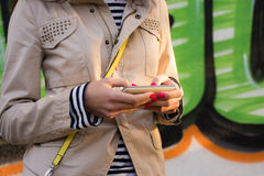 Young girl uses phone in the street. Young girl holding a mobile phone in her hands with red nail Polish. She is dressed in a beige jacket and a striped shirt Stock Photography