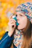 Asthma patient girl inhaling medication for treating shortness o. Young girl using asthma inhaler in a park - chronic disease control, allergy induced asthma Royalty Free Stock Images