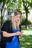 Young girl using cell phone. Pretty college girl busy texting on cell Stock Images