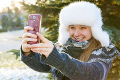 Young girl using cell phone in winter. Portrait of teenage girl taking selfie picture with mobile phone outside in winter Stock Photo