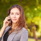 Young girl using cellphone outdoors. Youth woman talking like consultant. Chat business stock image