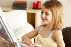 Young Girl Using Computer At Home Royalty Free Stock Images