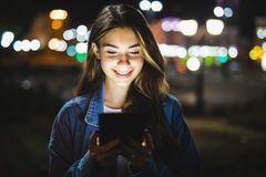 Young girl using digital tablet on night beauty light bokeh in city royalty free stock image