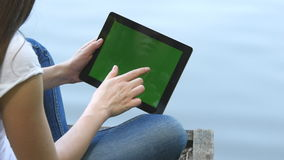 Young girl using digital tablet pc with green screen sitting on a wooden jetty by the lake. Rear view.. Young girl using digital tablet pc with green screen stock video footage