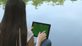 Young girl using digital tablet pc with green screen sitting on a wooden jetty by the lake. Rear view stock video