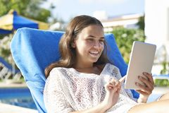 Young girl using digital tablet. While relaxing by swimming pool on vacation stock photo