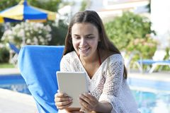 Young girl using digital tablet. While relaxing by swimming pool on vacation stock photography