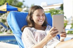 Young girl using digital tablet. While relaxing by swimming pool on vacation stock image