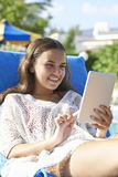 Young girl using digital tablet. While relaxing by swimming pool on vacation royalty free stock images