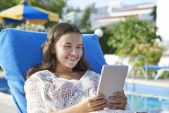 Young girl using digital tablet. While relaxing by swimming pool on vacation stock photos
