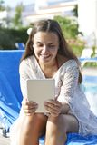 Young girl using digital tablet. While relaxing by swimming pool on vacation royalty free stock photos
