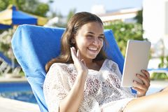 Young girl using digital tablet. While relaxing by swimming pool on vacation stock images