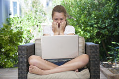 A young girl using her laptop outside. In the garden Royalty Free Stock Image