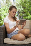 A young girl using her tablet outside. In the garden Royalty Free Stock Photography