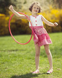 Young girl using hula hoop on arm in a park Royalty Free Stock Photography